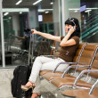 Woman with mobile phone in the airport — Stock Photo
