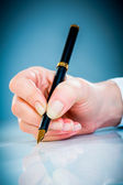 Woman's hand and pen — Stock Photo