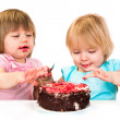 Two little baby girl eating cake — Stock Photo