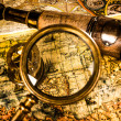 Royalty-Free Stock Photo: Vintage magnifying glass lies on an ancient world map