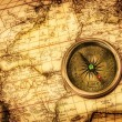 Vintage compass lies on an ancient world map. — Stock Photo #22942194