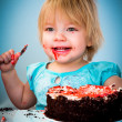 Little baby girl eating cake — Stock Photo