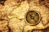 Vintage compass lies on an ancient world map. — Stock Photo