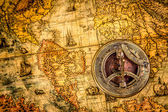 Vintage compass lies on an ancient world map — Stock Photo