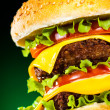 Stock Photo: Tasty and appetizing hamburger on darkly green