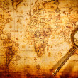 Vintage magnifying glass lies on an ancient world map — Stock Photo #24643501
