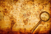 Vintage magnifying glass lies on an ancient world map — Foto Stock