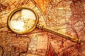 在古代世界地图上的复古放大镜谎言 — 图库照片