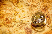 Vintage compass lies on an ancient world map. — Zdjęcie stockowe