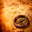 Vintage compass lies on an ancient world map. — Stock Photo #25930611