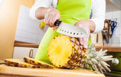 Woman's hands cutting pineapple — Stock Photo