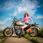 Biker girl sitting on motorcycle — Stock Photo #26523145