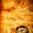 Vintage compass lies on an ancient world map. — Photo