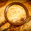 Vintage magnifying glass lies on an ancient world map — Stock Photo