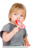 Baby eating a sticky lollipop — Stock Photo