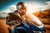 Biker racing on the road — Stock Photo
