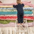 Stock Photo: Child climbs on bed - Princess and Pea.