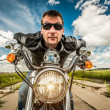 Stock Photo: Funny Biker racing on the road