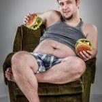 Fat man eating hamburger — Stock Photo #42312399