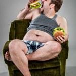 Fat man eating hamburger — Stock Photo #42312433