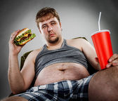 Fat man eating hamburger — Stock Photo