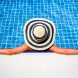 Woman in straw hat relaxing swimming pool — Stock Photo #43606523
