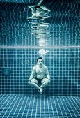 Man under water in a swimming pool to relax in the lotus positio — Stock Photo