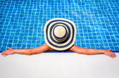 Woman in straw hat relaxing swimming pool — Stock Photo