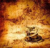 复古罗盘位于一个古老的世界地图. — 图库照片