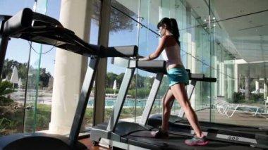 Kvinna kör på löpbandet i gym — Stockvideo