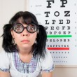 Funny woman wearing spectacles in an office at the doctor — Stock Photo #46742511