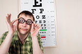 Funny manwearing spectacles in an office at the doctor — Stock Photo