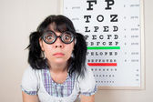 Funny woman wearing spectacles in an office at the doctor — Stockfoto