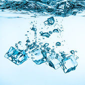 Ice cubes falling under water — Stock Photo