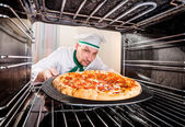 Chef cooking pizza in the oven. — Stock Photo