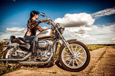 Biker girl and bike Harley Sportster — Stock Photo