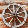 Wooden wheel from a cart against a rural log hut — Stock Photo #12571366