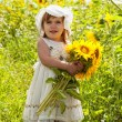 Little girl with a big bouquet of sunflowers in the field — Stock Photo