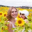 Happy mother with the daughter in the field with sunflowers — Stock Photo