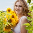 Happy mother with the daughter in the field with sunflowers — Stock Photo #12572123