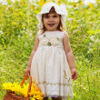 Little girl with a big wattled basket with sunflowers — Stock Photo