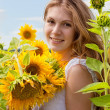 Happy mother with the daughter in the field with sunflowers — Stock Photo #12572125