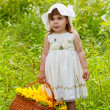 Little girl with a big wattled basket with sunflowers — Stock Photo #12572128