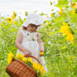 Little girl with a big wattled basket with sunflowers — Stock Photo #12572132