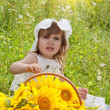 Little girl with a big wattled basket with sunflowers — Stock Photo #12572139