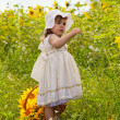Little girl with a big wattled basket with sunflowers — Stock Photo #12572141