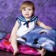 Little girl in a dress in sea style sits on color pillows — Stock Photo