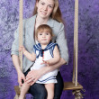 Mother swings the small daughter on a swing — Stock Photo #12572144