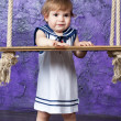 Little girl in a dress in sailor's style sits on a rope swing. Studio shooting. — Stock Photo