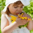 Royalty-Free Stock Photo: Little girl considers a big sunflower